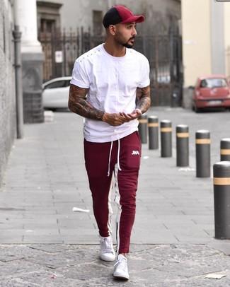 Come indossare e abbinare: t-shirt girocollo bianca, pantaloni sportivi bordeaux, sneakers basse bianche, berretto da baseball bordeaux