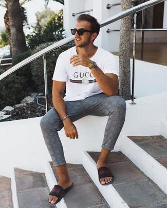 Come indossare e abbinare: t-shirt girocollo stampata bianca, chino scozzesi grigi, sandali in pelle a righe orizzontali neri, occhiali da sole neri