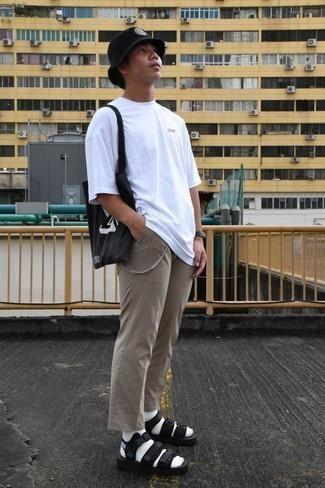 Trend da uomo 2020 quando fa molto caldo: Mostra il tuo stile in una t-shirt girocollo bianca con chino marrone chiaro per un look raffinato per il tempo libero. Se non vuoi essere troppo formale, opta per un paio di sandali di tela neri.
