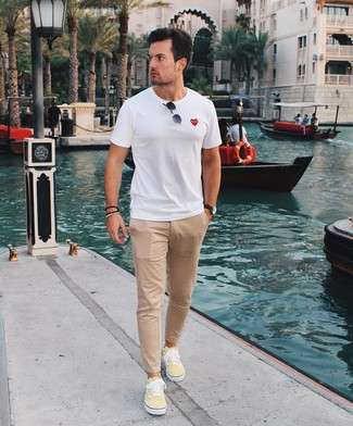Come indossare e abbinare: t-shirt girocollo bianca, chino marrone chiaro, sneakers basse di tela gialle, occhiali da sole neri