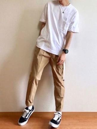 Moda ragazzo adolescente: Metti una t-shirt girocollo bianca e chino marrone chiaro per un look semplice, da indossare ogni giorno. Completa questo look con un paio di sneakers basse di tela nere e bianche.