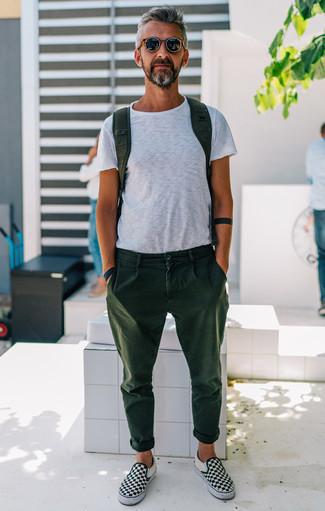 Moda uomo anni 40: Coniuga una t-shirt girocollo bianca con chino verde scuro per un look semplice, da indossare ogni giorno. Sneakers senza lacci di tela a quadri nere e bianche sono una interessante scelta per completare il look.