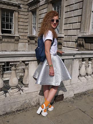 Come indossare e abbinare: t-shirt girocollo bianca, gonna a ruota argento, sandali con tacco in pelle pesanti bianchi, zaino di jeans blu scuro
