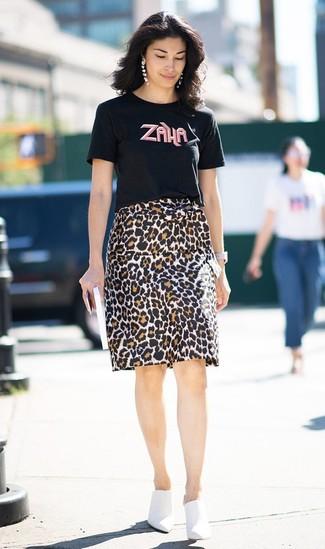 Come indossare: t-shirt girocollo stampata nera, gonna a tubino leopardata marrone, sabot in pelle bianchi, orologio in pelle bianco