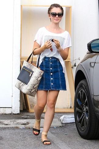 Come indossare: t-shirt girocollo stampata bianca e blu, gonna con bottoni di jeans blu, sandali piatti in pelle neri, borsa shopping in pelle con stampa serpente grigia