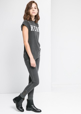 Moda ragazza adolescente in modo casual: Per creare un look adatto a un pranzo con gli amici nel weekend opta per una t-shirt girocollo stampata grigio scuro e jeans aderenti grigio scuro. Stivali chelsea in pelle neri sono una interessante scelta per completare il look.
