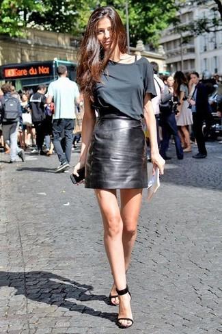 Come indossare: t-shirt girocollo grigio scuro, minigonna in pelle nera, sandali con tacco in pelle neri