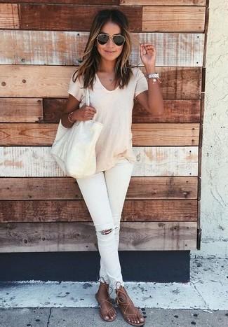 Come indossare: t-shirt girocollo beige, jeans aderenti strappati bianchi, infradito in pelle marroni, borsa shopping in pelle beige
