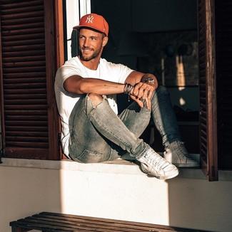 Come indossare e abbinare: t-shirt girocollo bianca, jeans aderenti strappati azzurri, sneakers alte in pelle bianche, berretto da baseball stampato rosso