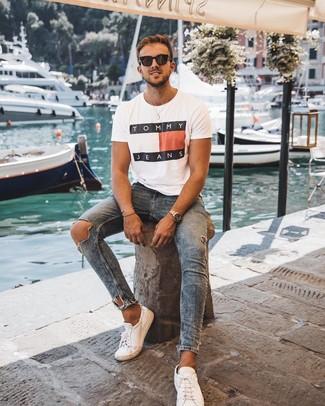 Come indossare e abbinare: t-shirt girocollo stampata bianca, jeans aderenti strappati blu, sneakers basse in pelle bianche, occhiali da sole neri