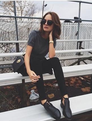 Come indossare: t-shirt girocollo grigio scuro, jeans aderenti neri, stivaletti in pelle tagliati neri, borsa a tracolla in pelle nera