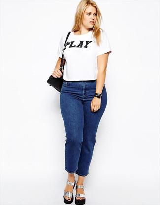 Come indossare e abbinare: t-shirt girocollo stampata bianca e nera, jeans blu, sandali con tacco in pelle pesanti argento, borsa a tracolla in pelle nera