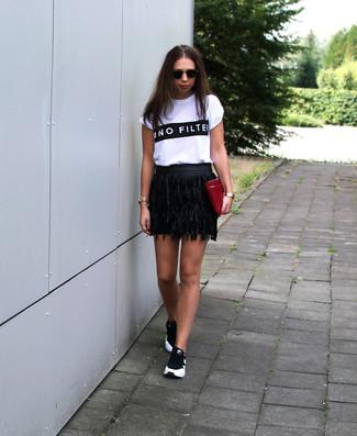Come indossare: t-shirt girocollo stampata bianca e nera, minigonna in pelle con frange nera, scarpe sportive nere e bianche, pochette in pelle bordeaux