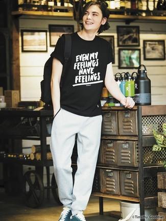 Come indossare e abbinare: t-shirt girocollo stampata nera e bianca, pantaloni sportivi grigi, sneakers basse in pelle scamosciata foglia di tè, zaino di tela nero