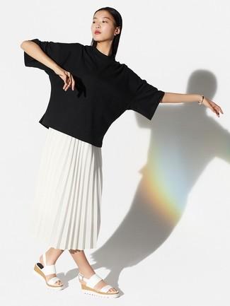 Come indossare: t-shirt girocollo nera, gonna longuette a pieghe bianca, sandali piatti in pelle bianchi