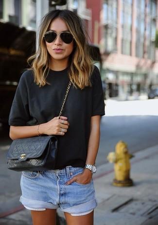 Indossa una t-shirt girocollo nera con pantaloncini di jeans azzurri per un look semplice, da indossare ogni giorno.