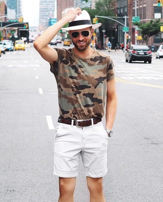 Come indossare e abbinare: t-shirt girocollo mimetica verde oliva, pantaloncini bianchi, borsalino di paglia bianco, cintura in pelle marrone scuro