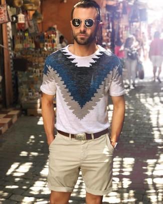 Come indossare e abbinare: t-shirt girocollo stampata bianca e blu scuro, pantaloncini beige, cintura in pelle marrone scuro, occhiali da sole neri