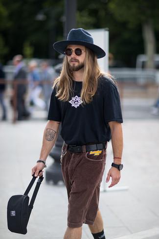 Come indossare e abbinare: t-shirt girocollo stampata nera e bianca, pantaloncini di velluto a coste marrone scuro, marsupio di tela nero, borsalino di lana blu scuro