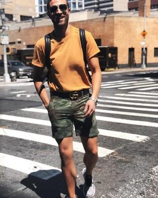 Come indossare e abbinare: t-shirt girocollo arancione, pantaloncini mimetici verde oliva, scarpe sportive grigie, zaino in pelle nero