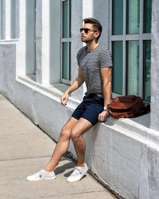 Come indossare e abbinare: t-shirt girocollo a righe orizzontali bianca e blu scuro, pantaloncini blu scuro, sneakers basse di tela bianche, zaino in pelle marrone