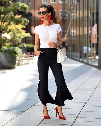 Come indossare e abbinare pantaloni a campana neri: Scegli un outfit composto da una t-shirt girocollo bianca e pantaloni a campana neri per un look spensierato e alla moda. Rifinisci questo look con un paio di décolleté in pelle scamosciata rossi.