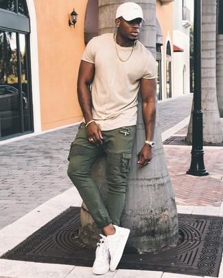 Come indossare: t-shirt girocollo beige, pantaloni cargo verde oliva, sneakers basse in pelle bianche, berretto da baseball bianco
