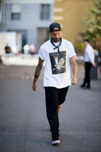Come indossare e abbinare: t-shirt girocollo stampata bianca e nera, pantaloni sportivi neri, sneakers basse nere, berretto da baseball nero