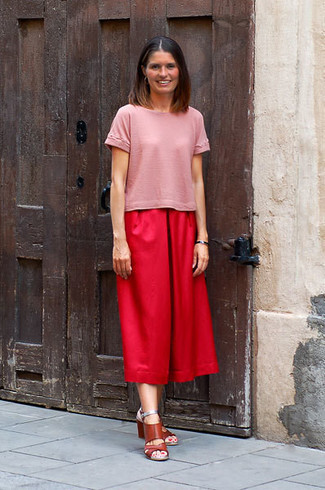 Come indossare e abbinare: t-shirt girocollo rosa, gonna pantalone rossa, sandali con tacco in pelle marroni