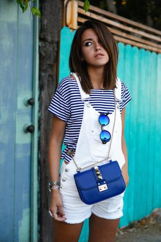 Come indossare e abbinare: t-shirt girocollo a righe orizzontali bianca e blu scuro, salopette corta di jeans bianca, borsa a tracolla in pelle blu, occhiali da sole blu