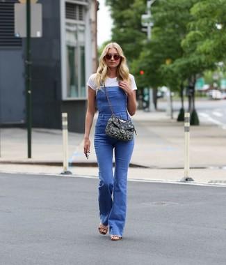 Come indossare: t-shirt girocollo bianca, salopette di jeans blu, sandali con tacco in pelle marrone chiaro, borsa a tracolla di tela decorata nera