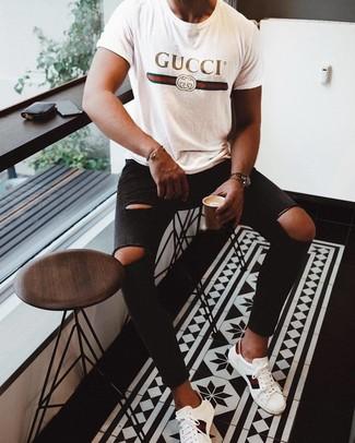 Come indossare e abbinare: t-shirt girocollo stampata bianca, jeans aderenti strappati neri, sneakers basse in pelle stampate bianche
