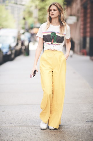 Come indossare: t-shirt girocollo stampata bianca, pantaloni larghi gialli, sneakers basse di tela bianche