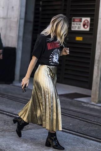 Come indossare: t-shirt girocollo stampata nera, gonna longuette a pieghe dorata, stivaletti in pelle neri