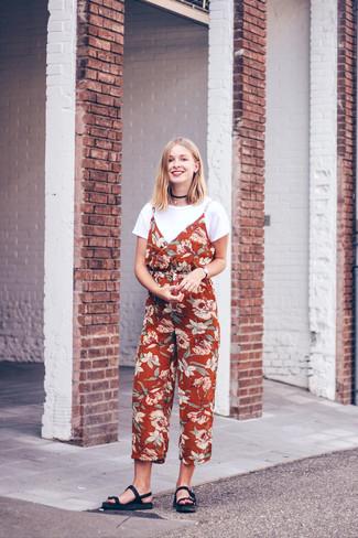 Moda ragazza adolescente: Indossa una t-shirt girocollo bianca e una tuta a fiori rossa per un look facile da indossare. Non vuoi calcare troppo la mano con le scarpe? Calza un paio di sandali piatti in pelle neri per la giornata.