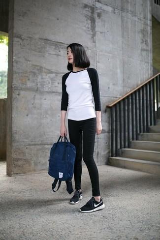 Come indossare: t-shirt manica lunga bianca e nera, jeans aderenti neri, scarpe sportive nere e bianche, zaino blu scuro