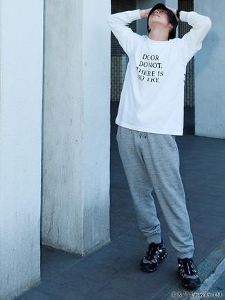 Come indossare e abbinare: t-shirt manica lunga stampata bianca e nera, pantaloni sportivi grigi, scarpe sportive nere, cappello alla pescatora nero