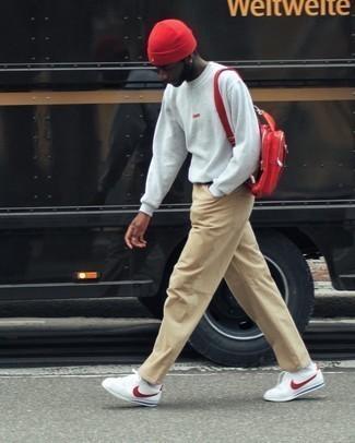 Trend da uomo 2020: Potresti abbinare una t-shirt manica lunga grigia con chino marrone chiaro per un look semplice, da indossare ogni giorno. Perfeziona questo look con un paio di sneakers basse in pelle bianche e rosse.