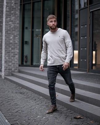 Moda uomo anni 20: Vestiti con una t-shirt manica lunga grigia e jeans aderenti grigio scuro per un look perfetto per il weekend. Perché non aggiungere un paio di chukka in pelle scamosciata marrone scuro per un tocco di stile in più?