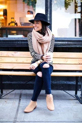 Come indossare: t-shirt manica lunga a righe orizzontali bianca e nera, jeans aderenti strappati blu scuro, stivaletti in pelle scamosciata marrone chiaro, borsalino di lana nero