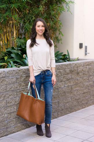 Come indossare: t-shirt manica lunga beige, jeans aderenti strappati blu, stivaletti in pelle scamosciata grigio scuro, borsa shopping in pelle terracotta