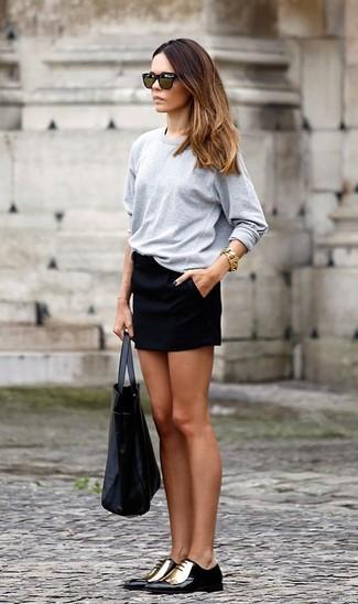 Come indossare e abbinare: t-shirt manica lunga grigia, minigonna nera, scarpe oxford in pelle nere e dorate, borsa shopping in pelle nera