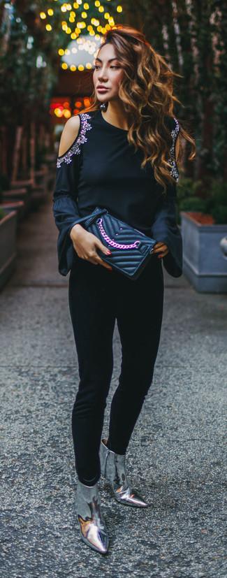 Come indossare: t-shirt manica lunga decorata nera, pantaloni skinny neri, stivaletti in pelle argento, pochette in pelle trapuntata nera