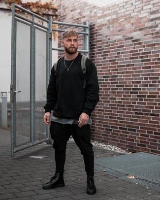 Moda uomo anni 20: Scegli un outfit composto da una t-shirt manica lunga nera e chino neri per un outfit comodo ma studiato con cura. Scegli uno stile classico per le calzature e prova con un paio di stivali casual in pelle neri.