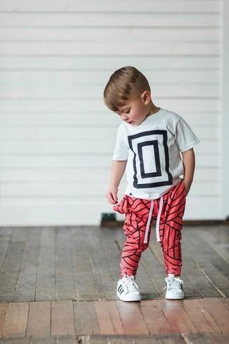 Come indossare e abbinare: t-shirt stampata bianca e nera, pantaloni sportivi rossi, sneakers bianche