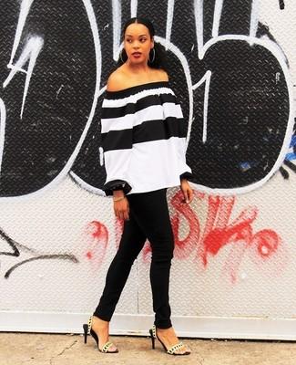 Come indossare: top con spalle scoperte a righe orizzontali bianco e nero, jeans aderenti neri, sandali con tacco in pelle dorati, bracciale dorato