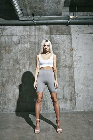 Come indossare: top corto bianco, pantaloncini ciclisti grigi, sandali con tacco in pelle bianchi, collana dorata