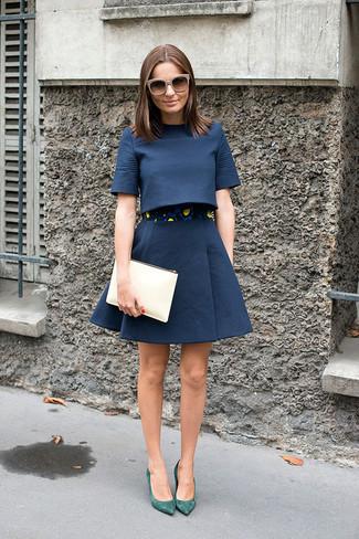 Come indossare: top corto blu scuro, gonna a ruota blu scuro, décolleté in pelle scamosciata verdi, pochette in pelle beige