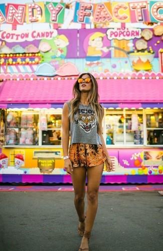 Come indossare: top corto stampato grigio, pantaloncini stampati arancioni, infradito in pelle marroni, occhiali da sole arancioni