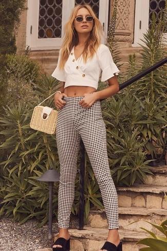 Come indossare e abbinare: top corto bianco, pantaloni skinny a quadretti neri e bianchi, sabot in pelle scamosciata neri, borsa a mano di paglia beige